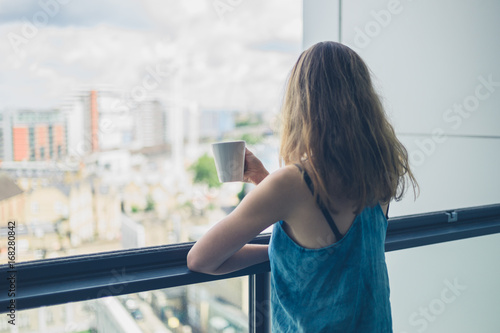 Fototapeta Woman with cup of coffee on balcony in city