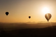 Silhouette of balloons with sunrise in background, aerial view