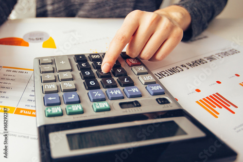 Closeup of Accountant Hands Using Calculator - Buy this
