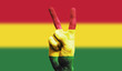 Bolivia national flag painted onto a male hand showing a victory, peace, strength sign