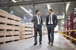 Two businessmen talking while walking in the factory