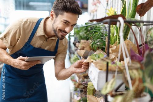 Fotografía  male florist with digital tablet