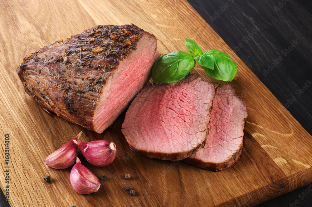 Fotografie, Obraz  Baked meat, garlic and basil on a wooden background. Roast beef.
