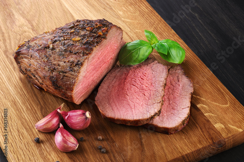 Fotografering  Baked meat, garlic and basil on a wooden background. Roast beef.