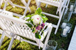 Beautiful wedding set up. Wedding ceremony in the garden. White wooden chairs decorated with flowers and candles standing in rows.
