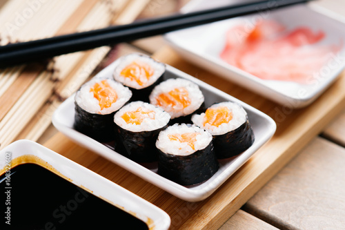 Obraz na plátně  Sushi rolls with salmon, chopsticks and dishes with soy sauce and ginger