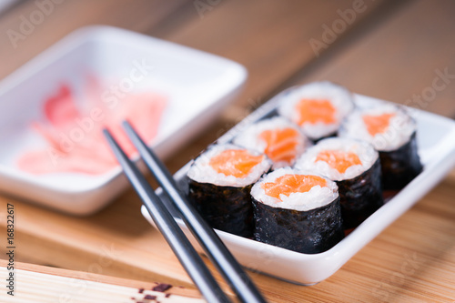 Foto  Sushi rolls with salmon, ginger and chopsticks