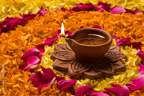 Flower Rangoli For Diwali Or Pongal Made Using Marigold Or Zendu Flowers And Red Rose Petals Over White Background With Diwali Diya In The Middle Selective Focus Buy This Stock Photo