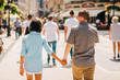 Multicultural Happy Couple Tourists Walking Down The Street Holding Hands | Honeymoon