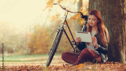 Girl is sitting under the tree with tablet.