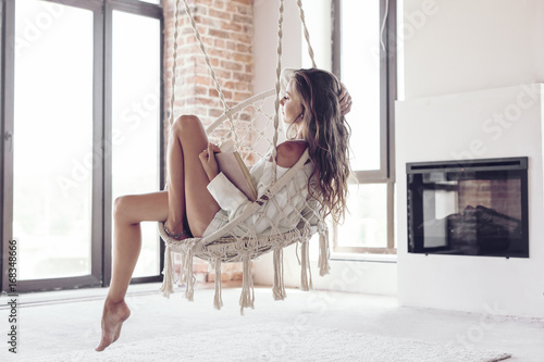 Fotografía  Woman relaxing at home in hanging chair