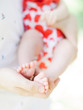 canvas print picture - baby's feet in father's hands