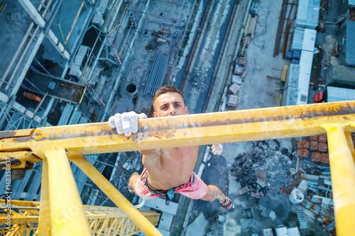 Fotografia, Obraz  Urban climbing: rock climber hanging on jib of construction crane with one hand
