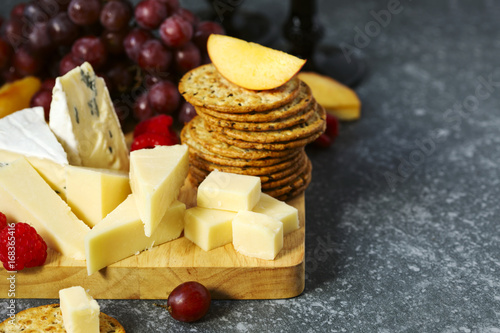 Cheese, creckers and fruits on wooden background Canvas-taulu