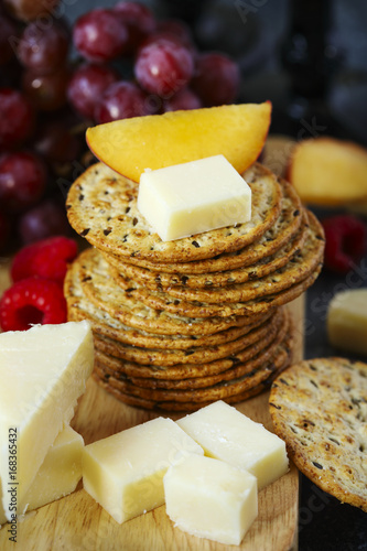 Cheddar cheese, creckers and fruits on wooden board Canvas-taulu