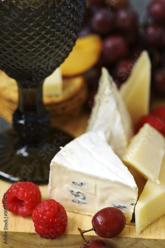 Fényképezés  Cheese, creckers and fruits on wooden background