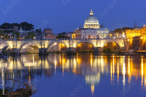 City on the water Saint Angel bridge and Saint Peter Cathedral with a mirror reflection in the Tiber River during morning blue hour in Rome, Italy.