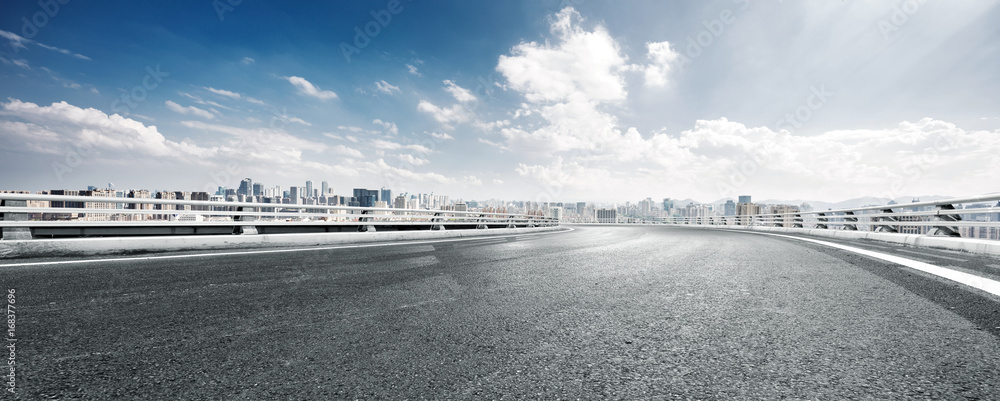 Fototapeta empty road and cityscape of modern city against cloud sky