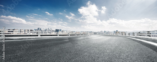 Fototapeta empty road and cityscape of modern city against cloud sky obraz
