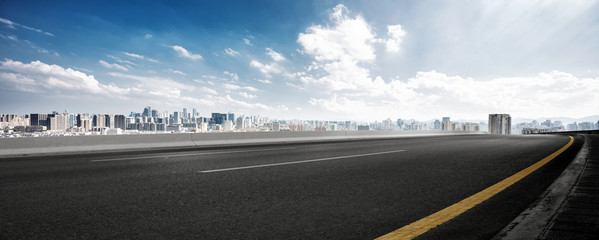 empty road and cityscape of modern city against cloud sky