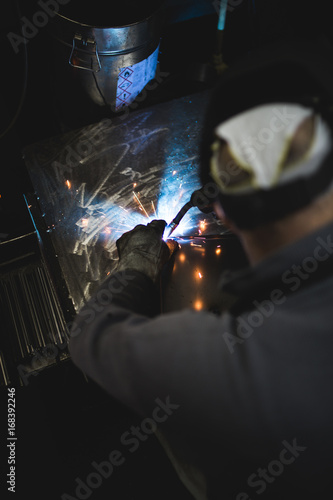 Metallurgy industry. Factory for production of heavy pellet stoves and boilers. Close up of manual worker welder on his job. Extremely dark conditions and visible noise.