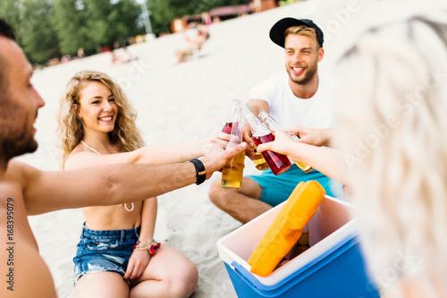 Plakat Grupa atrakcyjni młodzi ludzie cieszy się przy plażą pije i wznosi toast.
