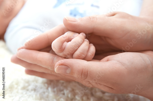 Staande foto Manicure Young mother holding hand of cute baby, closeup