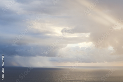 Rain and sun shining through the clouds over the Atlantic Ocean.