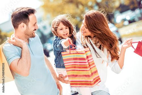 Plakat Uśmiechnięci rodzice i córka z torba na zakupy.