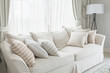 set of pillows on white classic sofa in living room
