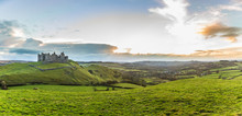 Countryside Panorama With Ruined Castle On A Hill At Sunset