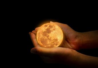 Female hand hold yellow full moon.