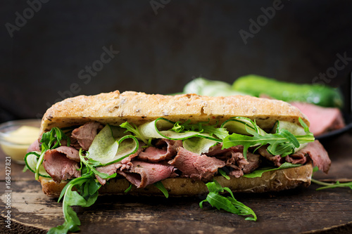 Staande foto Snack Sandwich of whole wheat bread with roast beef, cucumber and arugula
