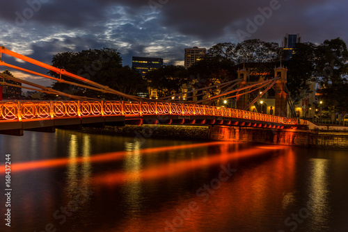 Old brightly illuminated bridge on the Singapore river at sunset  - 2 Poster
