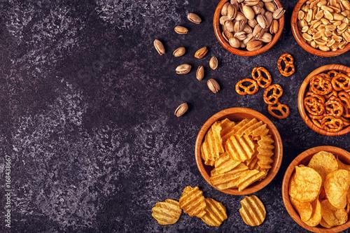 Fotografía  Snacks in a bowls on stone background.
