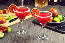 Two Blood Orange Margaritas With Salted Rims And Ingredients On Bar