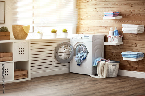 Interior of real laundry room with  washing machine at window at home Wallpaper Mural