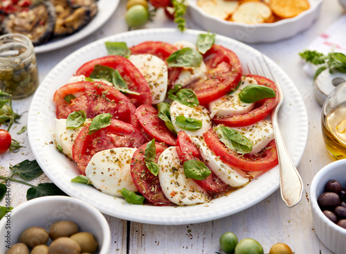Caprese salad made of sliced fresh tomatoes, mozzarella cheese and basil served on a white plate on a wooden table.Traditional Italian food