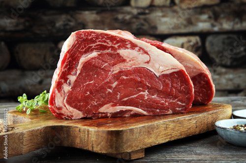 Fotografering  Raw fresh meat Ribeye Steak, seasoning and meat fork on dark background