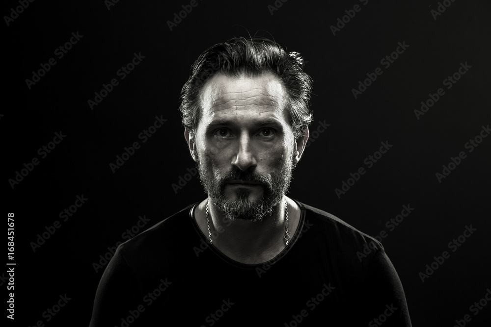 Fototapeta Monochrome portrait of mid aged lonely man. Black and white photo of male in black t-shirt on dark backdrop.