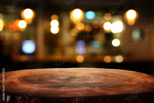 Fototapeta Image of wooden table in front of abstract blurred restaurant lights background obraz na płótnie