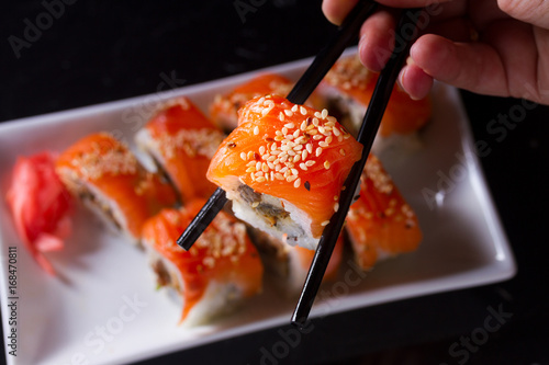 Fotografie, Obraz  Japanese sushi rolls dish with hand holding one pice in chopsticks on dark backg