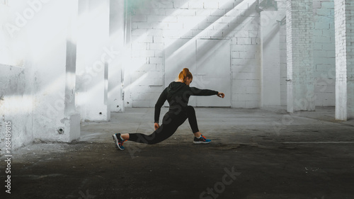 Caucasian female in sport outfit practicing karate, Japanese martial arts. Old warehouse indoor shot