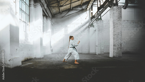Foto op Canvas Vechtsport Caucasian female in Kimono practicing karate, Japanese martial arts. Old warehouse indoor shot