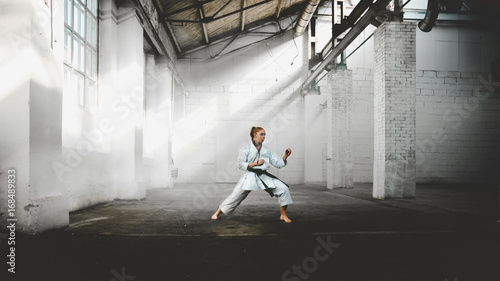 Garden Poster Martial arts Caucasian female in Kimono practicing karate, Japanese martial arts. Old warehouse indoor shot