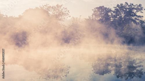 Plakat Dramatyczny morze mgła nad jeziorem z lasowym tłem przy mgławym wschodem słońca. Odbicie mglisty niebo i górski krajobraz.