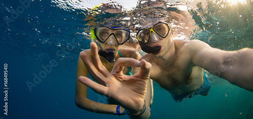 Young couple enjoying snorkeling underwater. Selfie portrait