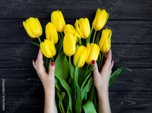 Foto op Canvas Bloemen Female hands holding yellow tulips on black vintage wooden table. Flat lay, top view