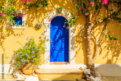 Photo Blue door of a yellow Greek house decorated with flowers, Assos town, Kefalonia