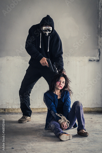 A terrorist man in mask holding gun kidnapping young women for a hostage in abandoned building Wallpaper Mural